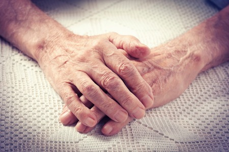 Care is at home of elderly. Old people holding hands closeup. Elderly man. photo