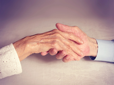 Old people holding hands closeup. Concept of loyalty love reliability many years together. Happy elderly couple man woman. photo