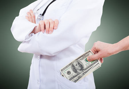 doctor giving dollars: Woman giving bribe to doctor, closeup isolated