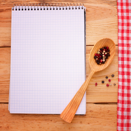 Pure notebook for recording menu, recipe on red checkered tablecloth tartan. Wooden table close up view from top photo