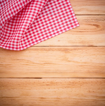 Pure notebook for recording menu, recipe on red checkered tablecloth tartan. Wooden table close up view from top