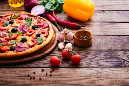 Pizza with ham peppers and olives with delicious fresh food on a wooden table. Ingredients tomatoes, salami and spices for pizza. photo