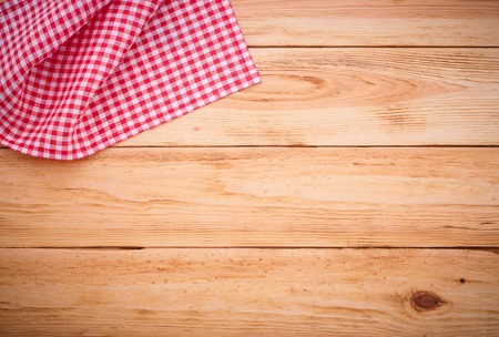 party table: Pure notebook for recording menu, recipe on red checkered tablecloth tartan. Wooden table close up view from top
