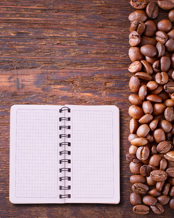 printed matter: Pure notebook for menu, recipe record on wooden table top view. Coffee beans as background for product pages of recipes and menus cookbooks