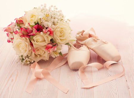 Ballet shoes. Pointe shoes on wooden background. Beautiful bouquet of white roses
