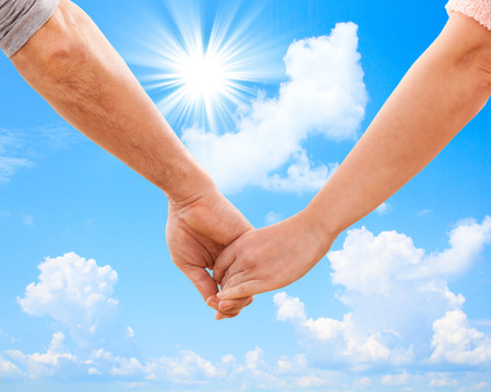 Happy couple holding hands close up. Sky and sun photo