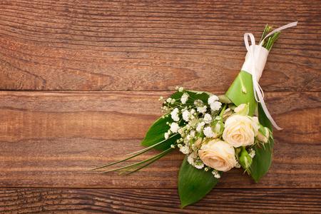 Blühender Zweig mit weißen zarten Blüten auf hölzernen Oberfläche. Hochzeitsringe, Hochzeitsstrauß Hintergrund. Standard-Bild