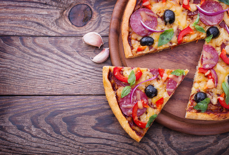 pizza slice: Pizza with ham, pepper and olives. Delicious fresh pizza served on wooden table.