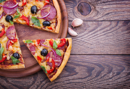 Pizza with ham, pepper and olives. Delicious fresh pizza served on wooden table. photo