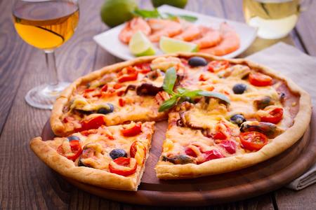 originality: Pizza with seafood. Seafood Italian Pizza slice on wood dish originality. Italian kitchen studio. Stock Photo