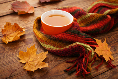 Autumn leaves, book and cup of tea on wooden table isolated on white background