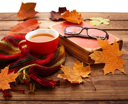 Hojas de otoño, el libro y la taza de té en la mesa de madera aislada sobre fondo blanco Foto de archivo - 32998214