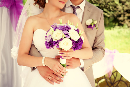 Happy bride and groom on their wedding. Wedding couple bride and groom holding hands.  Wedding bouquet closeup. photo