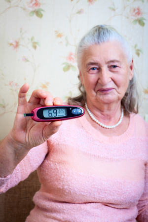 blood sugar: Woman testing for high blood sugar. Woman holding device for measuring blood sugar