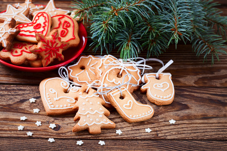 Christmas cookies handmade lies on wooden background. Gingerbread reindeer cookies and christmas decoration. Christmas tree photo