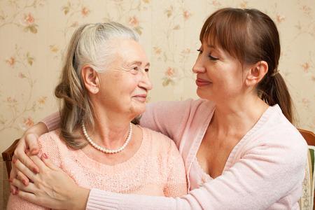 幸せな家族。高齢者の女性と喜んでカメラを見て大人の娘の肖像画。自宅介護者と年配の女性。