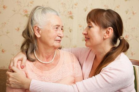 Gelukkig gezin. Portret van oudere vrouw en volwassen dochter gelukkig kijken naar de camera. Senior vrouw met haar verzorger thuis.