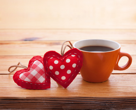 Cup of coffee and handmade heart of fabric on wooden table on Valentines Day . Love recognition. photo