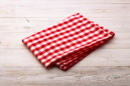 Top view of checkered tablecloth on white wooden table. Unique perspectives