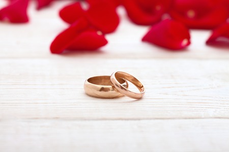 Wedding rings and wedding bouquet of red roses on wooden table. horizontally Stockfoto