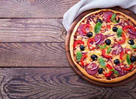 Delicious fresh pizza with ham, salami, tomato, pepper and olives served on wooden table. horizontal