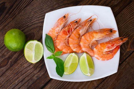 Delicious fresh seafood shrimp with lime on wooden table closeup top view horizontal