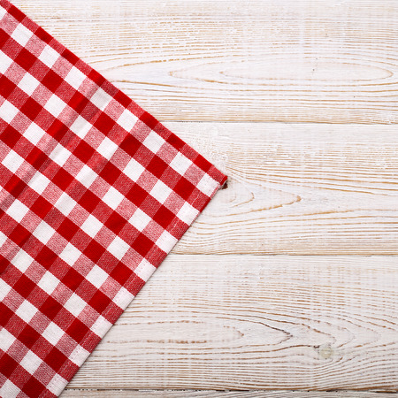 white napkin: Top view of checkered tablecloth on white wooden table. Unique perspectives