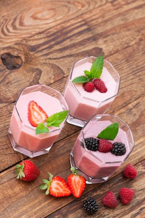 Drink smoothies summer strawberry, blackberry, raspberry on wooden table. photo