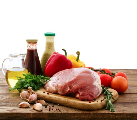 Raw pork meat with spices and vegetables isolated photo