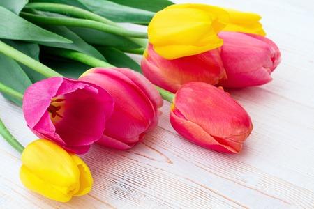 ramo de flores: Ramo de tulipanes de flores de primavera en el fondo de madera blanca