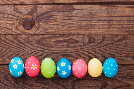 painted background: Easter eggs on wooden background. Holiday background.