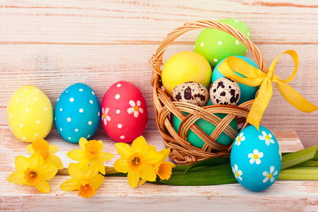 Easter eggs in basket with spring flowers photo