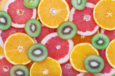 Orange, kiwi and grapefruit rings as background closeup. Stack of citrus pieces photo
