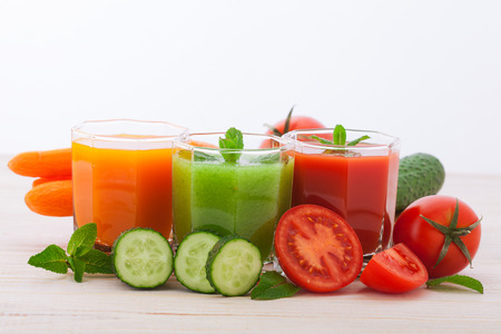 Tomato, cucumber, carrot Juices and vegetables on white wooden table photo