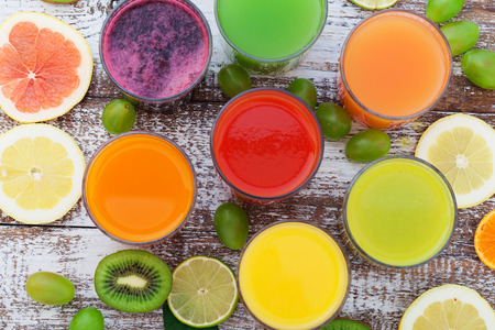 Glasses of tasty fresh juice, on wooden desk. Unusual top view Standard-Bild