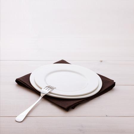 空の皿とディナー テーブル クロス ホワイト木製テーブルの上にカトラリー。
