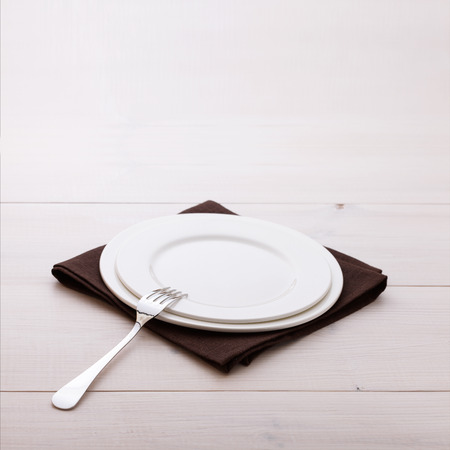 Empty plates and cutlery on table cloth on white wooden table for dinner.
