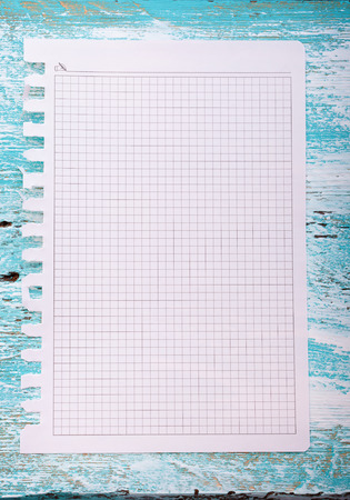 note booklet: blank page of paper on a wooden background