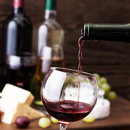 Red wine pouring into wine glass, close-up. Flat mock up for design. Stock Photo