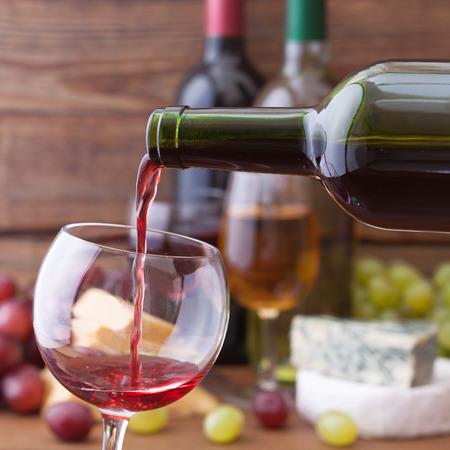 Red wine pouring into wine glass, close-up. Flat mock up for design. Reklamní fotografie