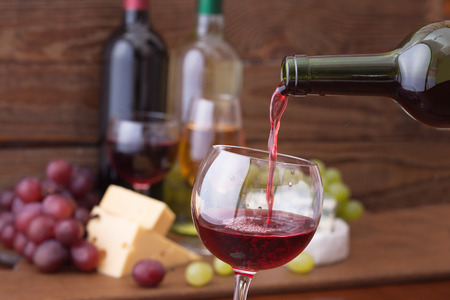 still life of wine: Red wine pouring into wine glass, close-up. Flat mock up for design. Stock Photo