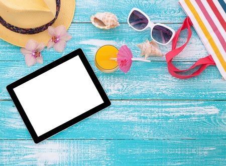 해변에 빈 빈 태블릿 컴퓨터입니다. 나무 배경 풀에 유행 여름 액세서리. 해변에 선글라스, 오렌지 주스와 플립 플롭. 열 대 꽃 난초입니다. 디자인 플