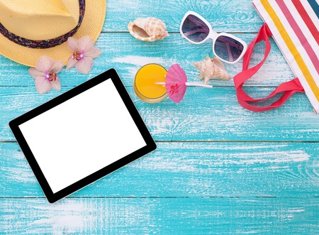 Blank empty tablet computer on beach. Trendy summer accessories on wooden background pool. Sunglasses, orange juice and flip-flops on beach. Tropical flower orchid. Flat mock up for design.