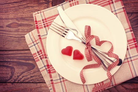 romantic places: Valentine day love beautiful. Romantic dinner, tableware and hearts on wooden background.