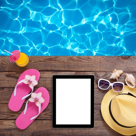 Blank empty tablet computer on beach. Trendy summer accessories on wooden background pool. Sunglasses, orange juice and flip-flops on beach. Tropical flower orchid. Flat mock up for design. photo