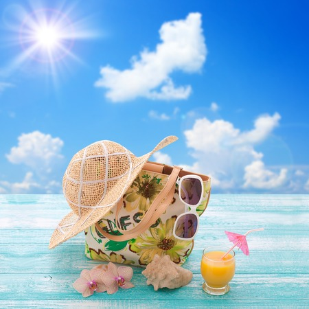 Fashionable clothes sunglasses, hat, flip-flops for beach holiday. Orange juice. Flat mock up for design. Top view. Summer vacation concept. photo