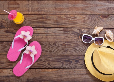 Fashionable clothes sunglasses, hat, flip-flops for beach holiday. Orange juice. Flat mock up for design. Top view. Summer vacation concept.