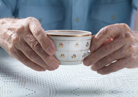 cup of tea: An elderly man drinks tea at home. Senior man holding cup of tea in their hands at table close-up