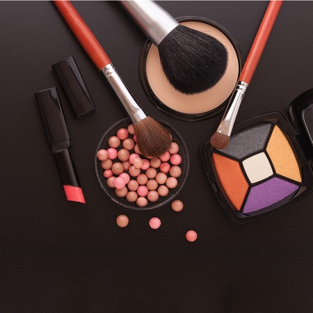 makeup artists: Various makeup products on dark background with copyspace Stock Photo