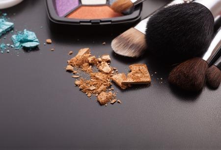 cosmeticos: Varios productos de maquillaje sobre fondo oscuro con copyspace